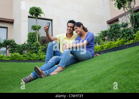 Couple taking a self portrait on a lawn - Stock Photo