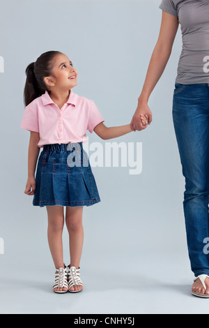 Young girl holding her mothers hand - Stock Photo