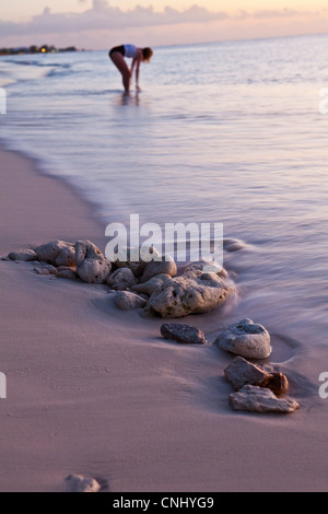 Woman standing at water's edge, Grand Cayman, Cayman Islands - Stock Photo