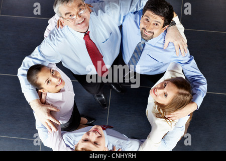 Colleagues with arms around each other - Stock Photo