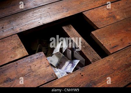 Money under floorboards - Stock Photo