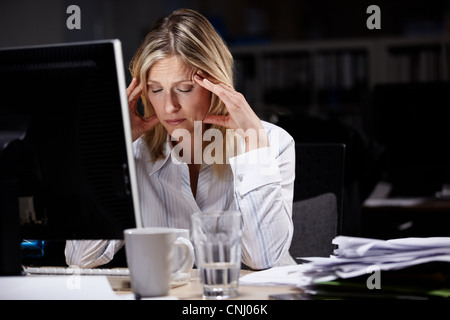 Stressed businesswoman working late - Stock Photo