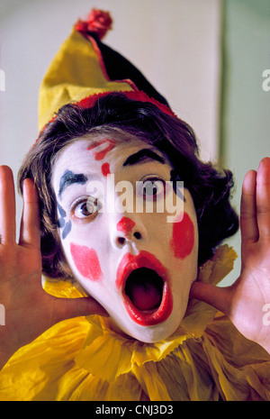 A young girl dresses up as a colorful circus clown to go trick-or-treating during the annual Halloween celebration - Stock Photo