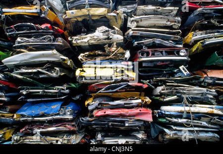 Old cars that have been mechanically crushed into scrap metal are stacked atop one another for recycling in Norway. - Stock Photo