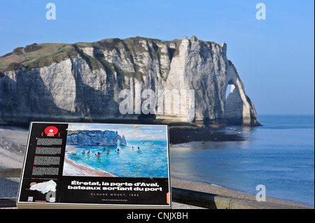 Sign showing painting by Claude Monet of the Porte D'Aval, a natural arch in the chalk cliffs at Etretat, Upper - Stock Photo