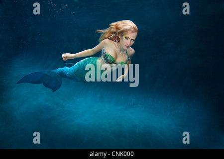 Blond mermaid swimming in pool, Virginia Beach, Virginia. - Stock Photo