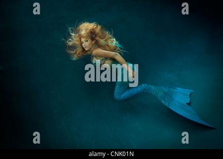 Blond mermaid swimming in pool, Virginia Beach, Virginia.