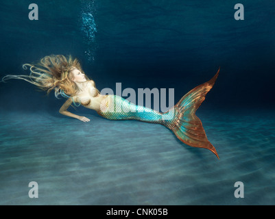 Young mermaid laying in the sand at the bottom of the sea - Stock Photo