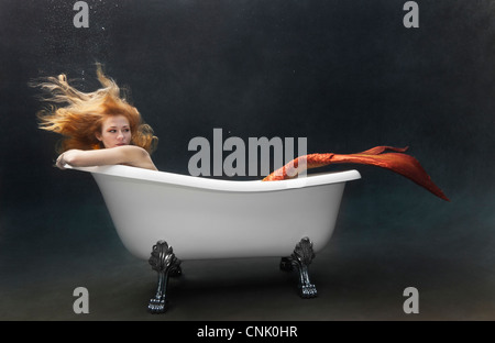 Mermaid laying underwater in her Victoria + Albert claw foot bathtub - Stock Photo