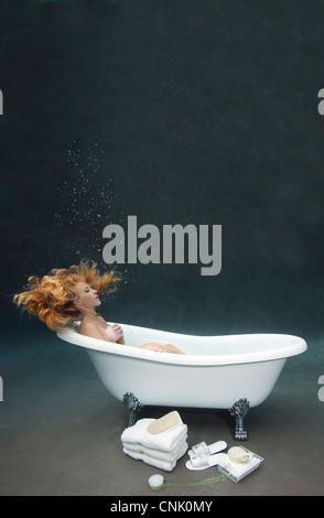 Young woman bathing herself underwater in her Victoria + Albert clawfoot bathtub - Stock Photo