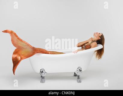 Mermaid bathing herself in her Victoria + Albert claw foot bathtub - Stock Photo