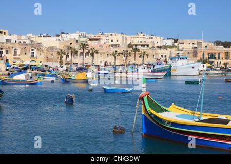 Colourful traditional wooden fishing boats within Marsaxlokk harbour, Malta, Europe - Stock Photo
