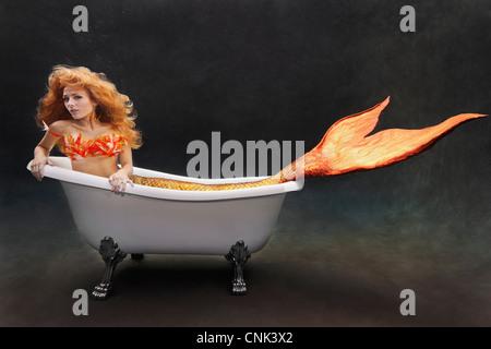 Young mermaid laying underwater in her Victoria + Albert bathtub - Stock Photo
