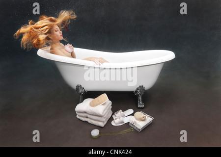 Young woman bathing herself underwater in her Victoria + Albert clawfoot bathtub