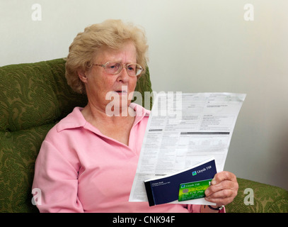 senior woman / pensioner shocked by credit card bill / bank statement - Stock Photo
