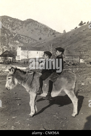 Two Small Town Brothers Riding Mule - Stock Photo