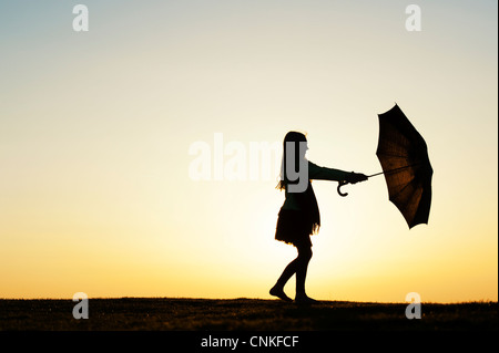 Young Girl spinning with an umbrella at sunset. Silhouette - Stock Photo