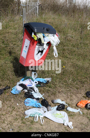 Overflowing Dog waste bin on beach footpath at Thorpeness Suffolk England - Stock Photo