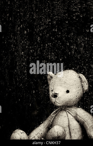 Sad Teddy bear looking through a window covered in rain drops. Sepia Toned. Still life - Stock Photo