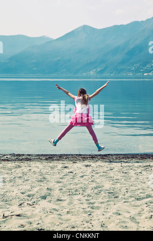 girl jumps in the air on a beach - Stock Photo