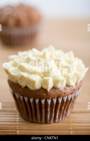 Delicious looking chocolate cupcake with vanilla frosting on bamboo placemat -shallow focus - Stock Photo