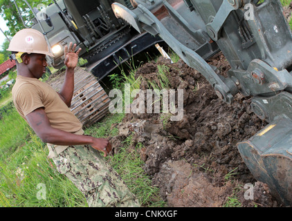 Equipment Operator 3rd Class Christopher Rawls guides an excavator during the construction of a bioswale, Monday, - Stock Photo