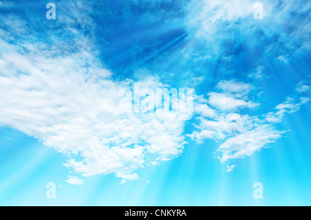 Sun rays through soft spring clouds on a blue sky shot with wide lens - Stock Photo
