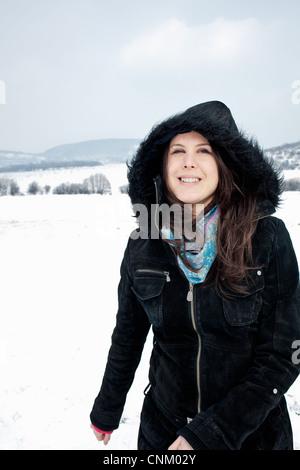 Woman in parka walking in snow - Stock Photo