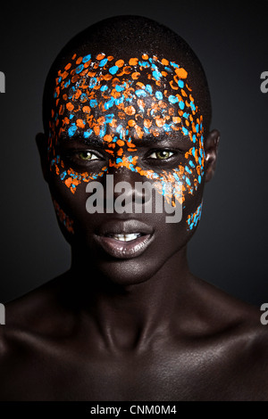 African Black young male model wearing creative orange and blue tribal paint on face, photographed in a studio environment. - Stock Photo
