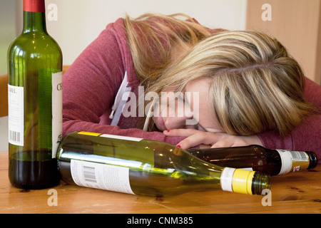 Young blonde alcoholic woman drunk, with empty bottles of alcohol, UK - Posed by a Model - Stock Photo