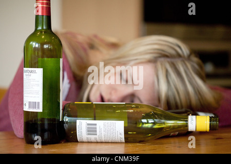 Young blonde alcoholic drunk woman, with empty bottles of alcohol, UK - Posed by a Model - Stock Photo