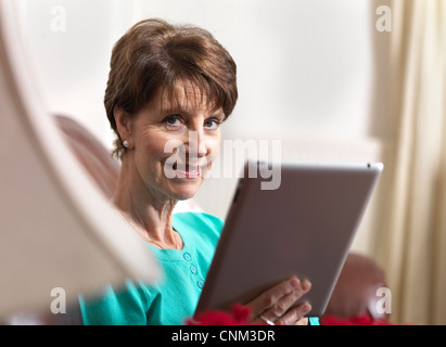 Senior attractive pensioner woman holding a tablet computer looking at camera sitting in her home. - Stock Photo