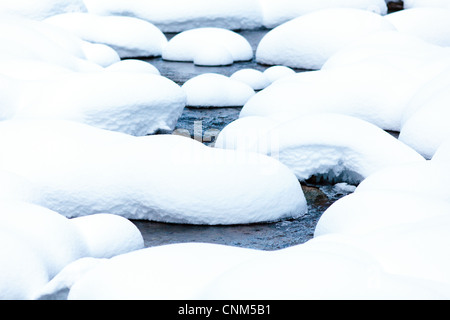 Creek flowing among boulders covered in snow - Stock Photo