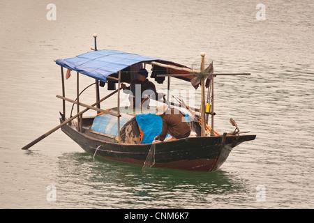 Two fishermen fishing in a small boat, Halong Bay, Quang Ninh, Vietnam - Stock Photo
