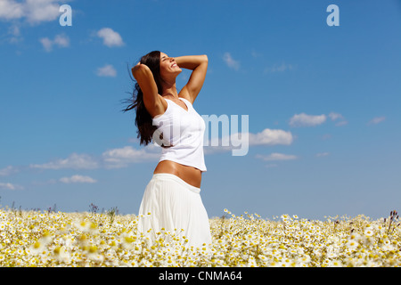 Young woman in white standing among chamomiles on a sunny day - Stock Photo