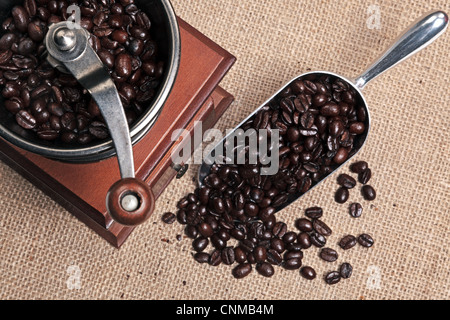 Photo of a hand operated traditional coffee grinder with a scoop full of arabica beans on a hessian background. - Stock Photo