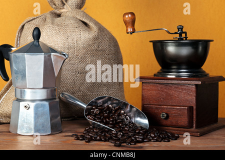 Still life photo of a caffettiera or moka pot with traditional coffee grinder hessian sack and arabica beans in - Stock Photo
