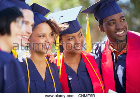 Graduates smiling together in cap and gown - Stock Photo