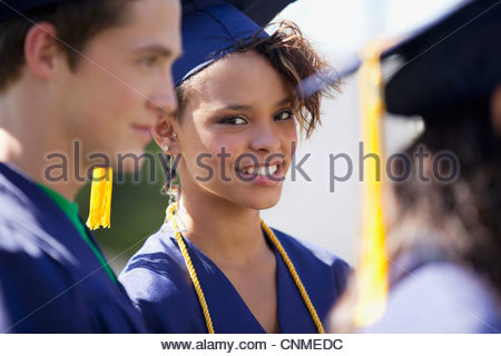 Graduate smiling in cap and gown - Stock Photo