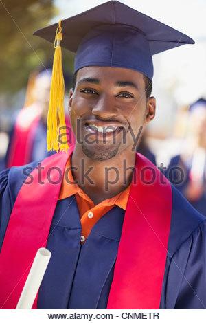 Smiling graduate holding diploma - Stock Photo