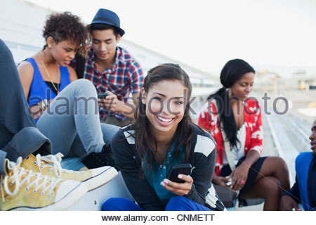 Students sitting together on bleachers - Stock Photo
