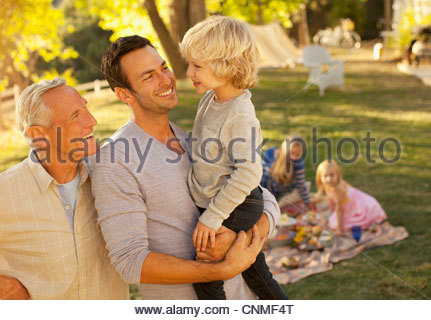 Three generations of men talking outdoors - Stock Photo