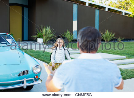 Girl in fairy wings running to father - Stock Photo