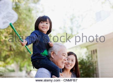 Older man carrying grandson on shoulders - Stock Photo