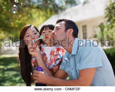 Family blowing bubbles together outdoors - Stock Photo