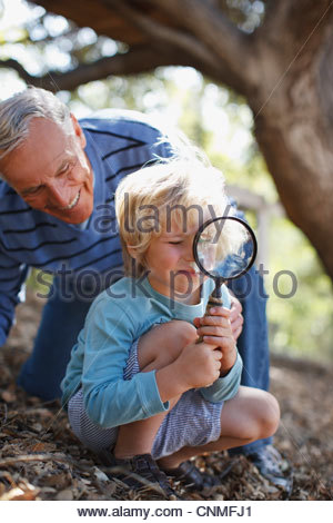 Older man and grandson using magnifying glass - Stock Photo