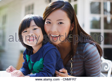 Mother and son sitting together outdoors - Stock Photo