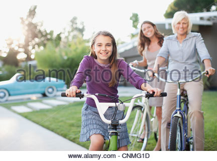 Three generations of women riding bicycles - Stock Photo