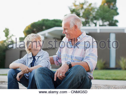 Older man and grandson sitting together - Stock Photo