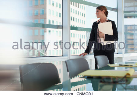 Businesswoman admiring view from office window - Stock Photo